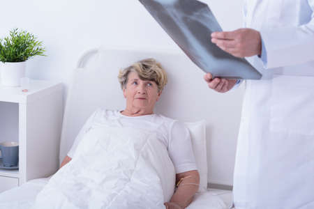 cheerless: Doctor is looking at the x-ray image of his patient Stock Photo