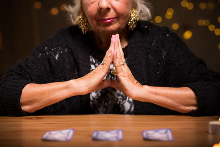 spirit medium: Old fortune teller knows how to cheat her clients Stock Photo