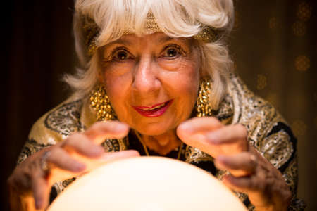 Old fortune teller is strange with her crystal ball