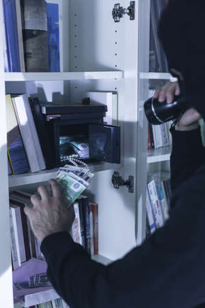 housebreaking: Robber breaking into a safe at night