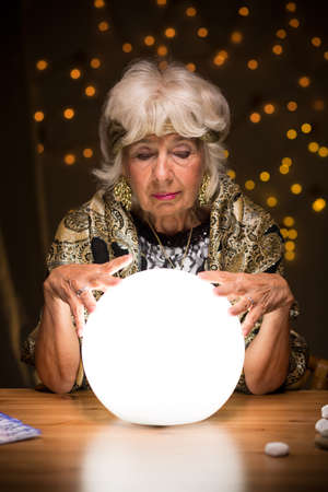 trustful: Old fortune teller sees a future from the crystal ball