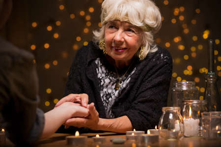 enchantment: Old fortune teller sees a future from lifelines Stock Photo