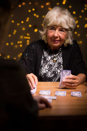 trustful: Old fortune teller sees a future of her client