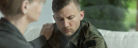 war: Psychologist comforting and supporting young soldier with trauma Stock Photo