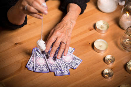 Old fortune teller is choosing a card for her client