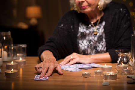 spiritualist: Old fortune teller is giving a card to her client Stock Photo