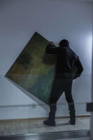 Mannelijke dief het stelen van dure schilderij 's nachts Stockfoto