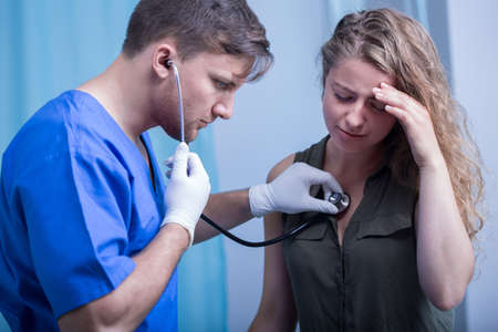 diagnosing: Image of doctor with stethoscope diagnosing patient Stock Photo