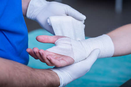 Close-up of male doctor bandaging a hand Stock Photo