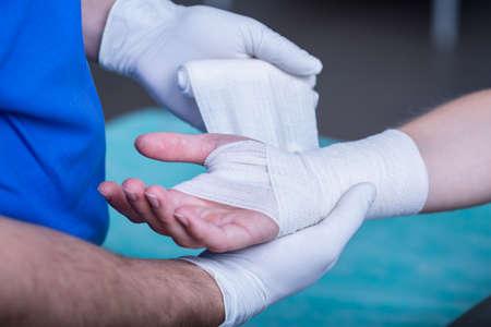 herida: Primer plano de médico hombre vendar una mano
