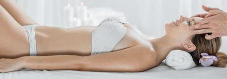 head massage: Panorama of woman in white bikini during head massage
