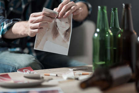 ex: Drunk boy tearing up a photo of ex girlfriend