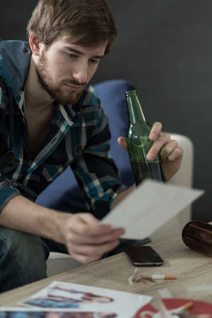 heartbroken: Heartbroken young guy drinking beer  and looking on the photos