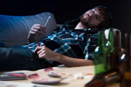 joven fumando: Drogas Intoxicado adicto tipo con una articulación Foto de archivo