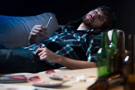 smoking marijuana: Intoxicated drug addicted guy with a joint Stock Photo