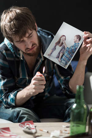 heartbroken: Young desperate heartbroken guy destroying love photos