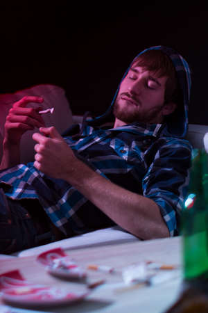 Young drugged man smoking a joint alone at home Stock Photo