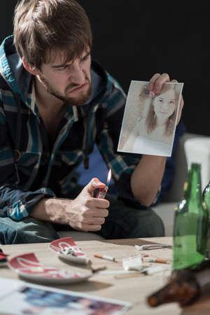 hombre tomando cerveza: Hombre enojado quemar una foto de su ex novia
