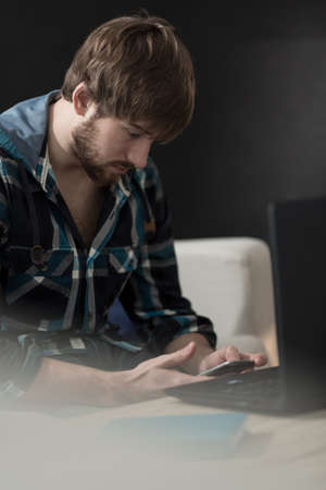 homme triste: Jeune homme envoyant un message sur son smartphone Banque d'images