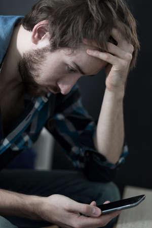 persona triste: Individuo joven que recibe un mensaje de texto ruptura