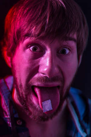 Guy with LSD blotter stamp on the tongue