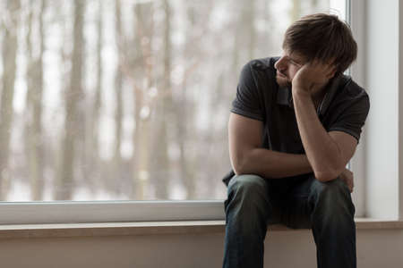 Young miserable depressed man sitting and thinking Standard-Bild