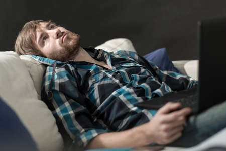 homme triste: Homme ennuyé avec un ordinateur portable sur le canapé Banque d'images