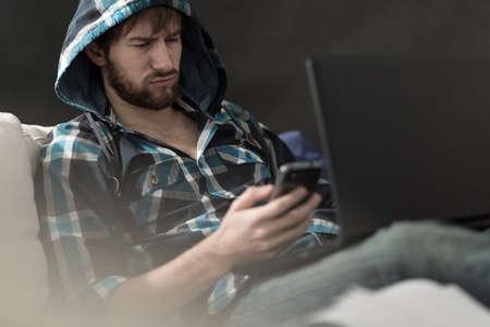 novios enojados: Hombre irritado la lectura de un mensaje de texto de su novia Foto de archivo