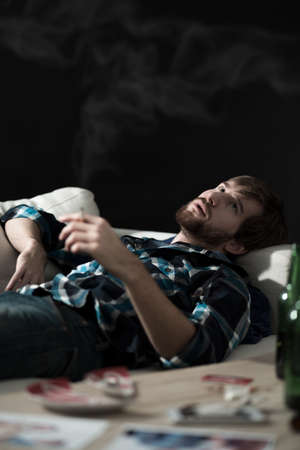 junkie: Young addicted junkie guy lying on the sofa and smoking weed Stock Photo
