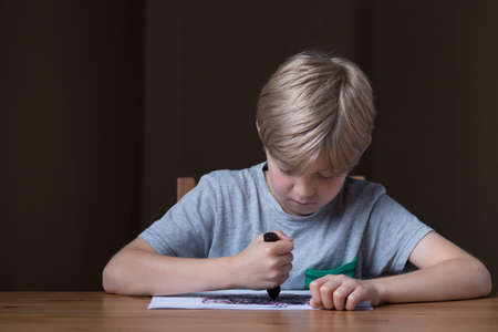 heartbreaking: Young boy is lacing into a drawing