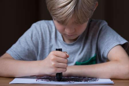 garabatos: El muchacho joven est� dibujando durante su terapia Foto de archivo