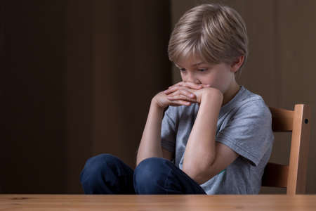 maltreatment: Little boy feels vey lonely in his house Stock Photo