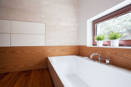White porcelain bath in modern wooden washroom