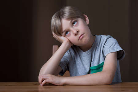 Young boy is very bored because of rain Stock Photo