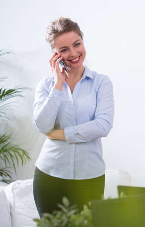 hear business call: Happy businesswoman is talking on the phone Stock Photo
