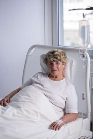 female catheter: Elderly woman is lying in hospital and smiling Stock Photo