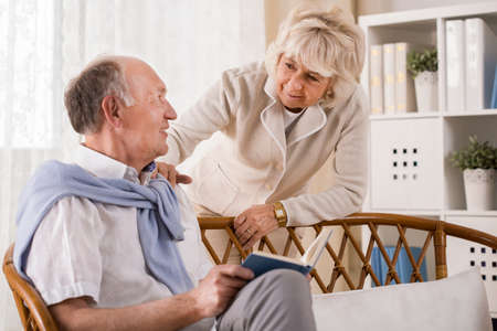 he: Old woman is asking her husband if he wants anything Stock Photo