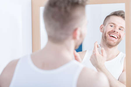 narcissistic: Photo of young smiling man admiring his mirror reflection Stock Photo
