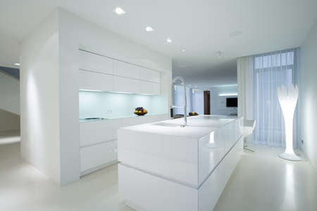 Horizontal view of white gleaming kitchen interior