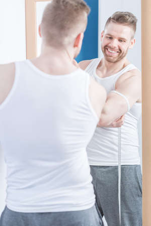 narcissistic: Picture of smiling muscular narcissistic male measuring his biceps