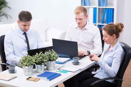 empleados trabajando: Empleados de oficina están trabajando en emabrgo ordenadores portátiles en la oficina