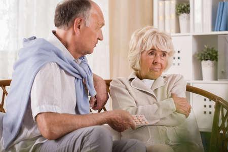 stubborn: Old man is giving his stubborn elder wife medicine