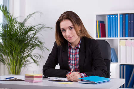 work experience: Photo of smiling female office worker sitting at desk