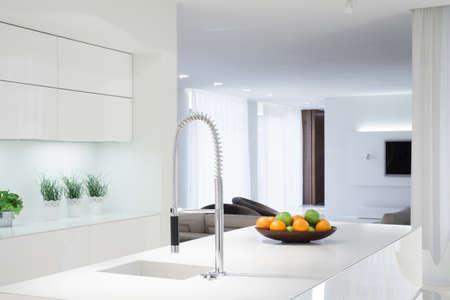 色の詳細を持つ白いキッチンを間します。