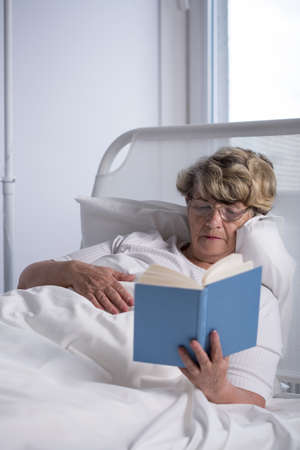 open  women: Female patient is reading an interesting book Stock Photo