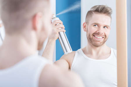 undershirt: Portrait of stylish content male spraying his trendy haircut