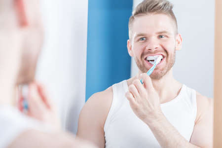 narcissistic: Picture of muscular narcissistic male brushing teeth Stock Photo
