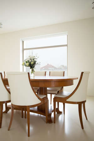 dining table and chairs: Wooden dining table in bright luxury interior Stock Photo