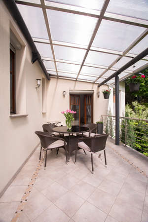 garden furniture: Image of a covered terrace with elegant garden furniture Stock Photo