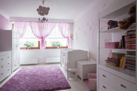 Photo of neat furnished child room with pink rug